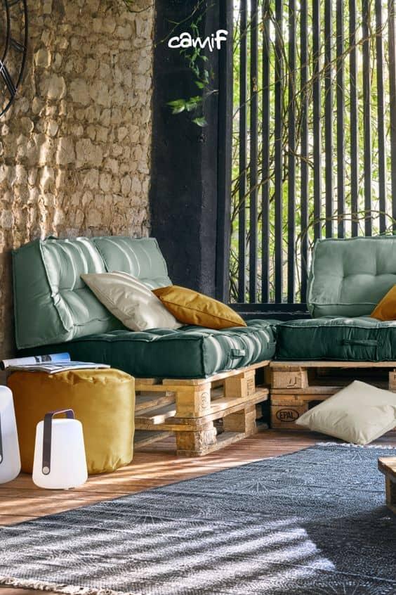 Un canapé en palette de bois et des coussins verts